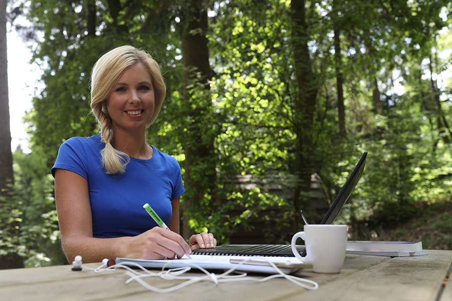 Een afbeelding van een sfeerbeeld op wifi4all.nl waarop een vrouw met een laptop aan een picknicktafel werkt doordat zij snel internet in het buitengebied heeft.
