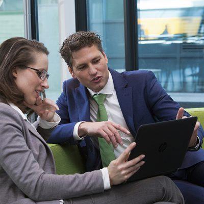 Een sfeerbeeld van een man in een blauw pak die wat aanwijst op een tablet aan de vrouw die links bij hem op een groene bank zit.