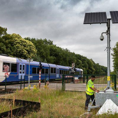 Een sfeerbeeld van een monteur die langs het spoor onderhoud pleegt aan een mobiele cameramast.